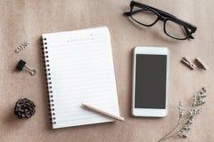 Tom anteckningsbok med mobiltelefonen på skrivbordkontor i workspace Royaltyfri Foto