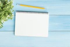 Tom anteckningsbok med och blyertspenna på blå bakgrund, lekmanna- foto för lägenhet royaltyfria foton
