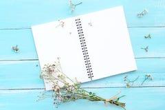 Tom anteckningsbok och bukett av lösa blommor på blå träbakgrund arkivbilder