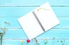 Tom anteckningsbok och bukett av lösa blommor på blå träbakgrund royaltyfri fotografi