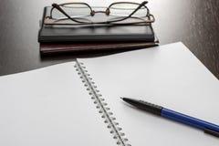Tom anteckningsbok och exponeringsglas Arkivbild