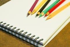 Tom anteckningsbok och färgrika blyertspennor på brun bakgrund, målningmaterial arkivfoto