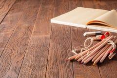 Tom anteckningsbok och färgrika blyertspennor på trätabellen Radergummi och träben royaltyfri foto