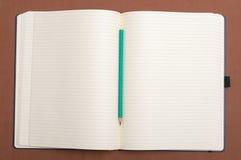 Tom anteckningsbok och grön blyertspenna Royaltyfri Fotografi