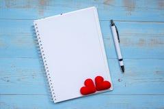 Tom anteckningsbok och penna med för hjärtaform för par röd garnering på blå trätabellbakgrund Gifta sig romantiskt och lyckligt royaltyfria foton