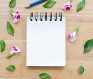 Tom anteckningsbok på wood bakgrund med blommor Royaltyfri Fotografi