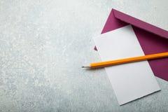 Tom bokstav, purpurfärgat kuvert och blyertspenna på en vit bakgrund för tappning kopiera avstånd royaltyfri bild