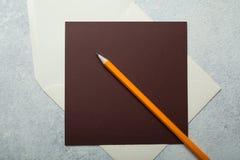 Tom brevhuvud och orange blyertspenna på vit tappningbakgrund royaltyfri fotografi