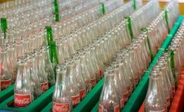 Tom coca - colaflaskor höll i fabrikslagring, royaltyfri bild