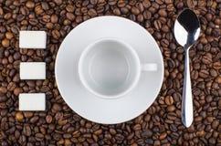 Tom coffeecup med tefatet, klimpigt socker och skeden på kaffe Royaltyfria Foton