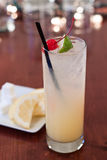 Tom Collins. Traditional tom collins served on a bar top in a tall glass with cherry and lime wedge garnish Stock Images