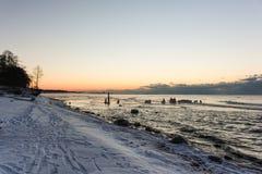 Tom cor-de-rosa do por do sol no céu, na praia nevado e no cais de madeira velho Fotos de Stock Royalty Free