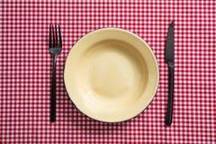 Tom emaljplatta, gaffel och kniv på den röda rutiga bordduken, bästa sikt arkivbild