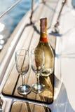 Tom exponeringsglas och flaska med champagne med havsbakgrund royaltyfri foto