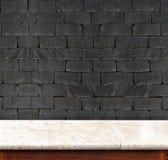 Tom för marmortabell och svart tegelstenvägg för vit i bakgrund pro royaltyfria bilder