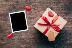 Tom fotoram och gåvaask med röd hjärta på wood bakgrund Royaltyfri Fotografi