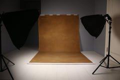 Tom fotostudio med lightingutrustning Grå färg- och brwonbakgrund arkivbild