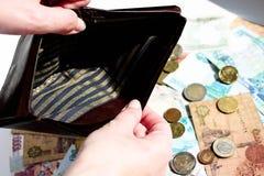 Tom gammal plånbok i de kvinnliga händerna över bakgrund som är full av pengar och mynt Inget pengarbegrepp arkivbilder