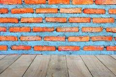 Tom gammal trägolvförgrund för produktplacering med nybyggd bakgrund för vägg för röd tegelsten arkivfoto