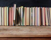 Tom gammal trätabell på en bakgrund av böcker arkivfoto