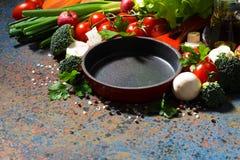 Tom gjutjärnkastrull och nya organiska grönsaker royaltyfria bilder