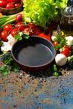 tom gjutjärnkastrull och nya organiska grönsaker, lodlinje royaltyfri foto