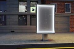 Tom glödande affischtavla på den tomma gatan på natten Arkivfoto