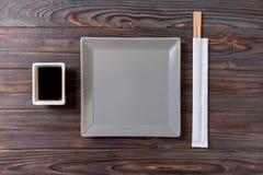 Tom grå fyrkantig platta med pinnar för sushi på träbakgrund B?sta sikt med kopieringsutrymme royaltyfri foto