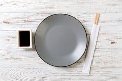 Tom grå rund platta med pinnar för sushi och soya på träbakgrund B?sta sikt med kopieringsutrymme royaltyfria bilder