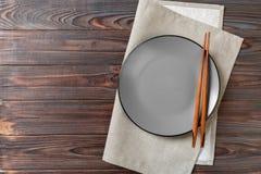 Tom grå rund platta med pinnar för sushi och soya på träbakgrund B?sta sikt med kopieringsutrymme arkivbild