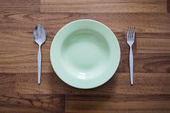 Tom grön maträtt med den rostfria gafflar och skeden, på Wood texturbakgrund Arkivfoton