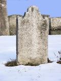 Tom gravsten i snöig kyrkogård Arkivfoto