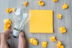Tom gul anmärkning och smulat papper med affärsmaninnehavlightbulben på trätabellbakgrund Ny idé som är idérik, innovation arkivfoto