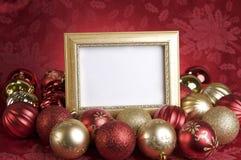 Tom guld- ram med julprydnader på en röd bakgrund Arkivbilder