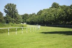 Tom hästracerbana, behandlat grönt gräs och vita stänger på t arkivfoton