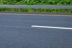 Tom huvudväg med den delande linjen, vägrenen och grönt gräs Fotografering för Bildbyråer