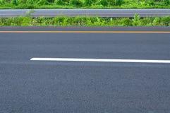 Tom huvudväg med den delande linjen, vägrenen och grönt gräs Arkivbilder
