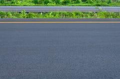 Tom huvudväg med den delande linjen, vägrenen och grönt gräs Royaltyfri Foto