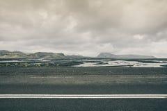 tom iceland väg Sikt med steniga berg i backgrouen arkivfoto