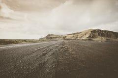 tom iceland väg Sikt med steniga berg i backgrouen royaltyfria bilder