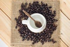 Tom kaffekopp som omges av kaffebönor Royaltyfria Foton