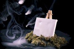 Tom kanfas på staffli med torkade cannabisknoppar som isoleras över bla Arkivbild
