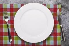 Tom keramisk platta av vit färg och bestick på en rutig bordduk royaltyfri bild