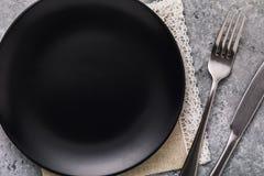 Tom keramisk plattasvartfärg med en gaffel och en kniv på en tabell många bakgrundsklimpmat meat mycket arkivbilder