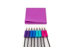 Tom klibbig anmärkning för rosa färger på vit bakgrund med färgglade pennor Royaltyfri Foto