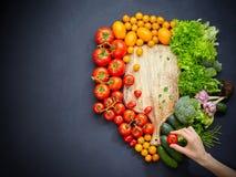 Tom lantlig skärbräda som omges av olika färgrika grönsaker på den svarta tabellen arkivfoto
