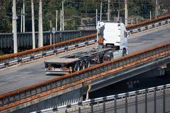 Tom lastbil på vägen, ritter upp över bron, industriell infrastruktur och järnväg i havsport, lasttrans., leverans Arkivfoto