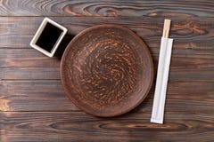 Tom mörk tappningrundaplatta med pinnar för sushi på träbakgrund B?sta sikt med kopieringsutrymme royaltyfria bilder