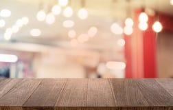 Tom mörk trätabell framme av abstrakt suddig bokehbakgrund av restaurangen Kan användas för den dina skärm eller montagen arkivbild