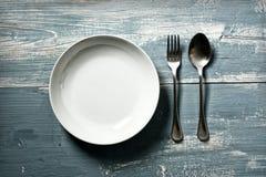 Tom maträtt med gaffeln och sked på den blåa tabellen - tappningeffekt royaltyfri fotografi